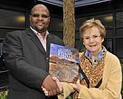 Table Mountain Fund's Manager, Cliff Dlamini, presenting TMF's recently published coffee table book to Ald. Belinda Walker.