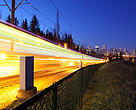A light rail transit train, powered by wind-generated electricity and part of the city's public transit system, rushes through on its dedicated rail line into the downtown core of the city, Calgary, Alberta, Canada.