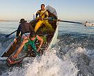 Small-scale fishers rowing the waves - image by Peter Chadwick