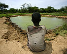 Child overlooking a dam built in his village in Kenya, where access to water is a major challenge facing farmers